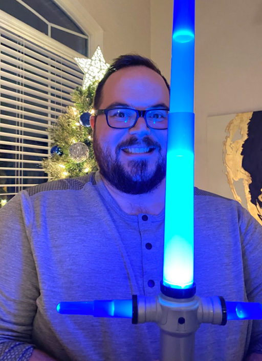 Jonathan Irvin holding a blue lightsaber in front of a glowing Christmas tree.
